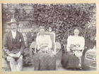 [Unidentified family seated outdoors with pet cats and bird]