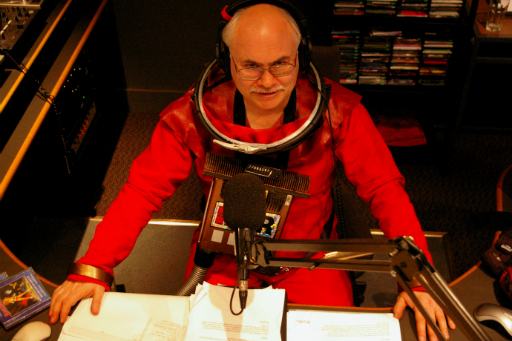 Colour photo of bald man with glasses wearing a spacesuit at a radio mixing desk with microphone