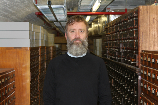 Portrait of bearded man wearing black jumper standing in a basement in front of wooden catalogue drawers