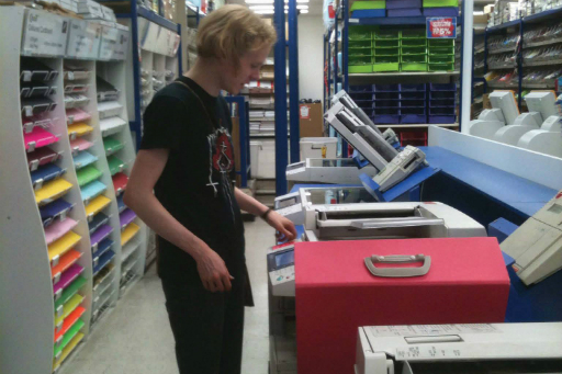 Colour photo of man with blond hair wearing a black T-shirt standing at a photocopier in a stationery store with equipment and multi-coloured paper
