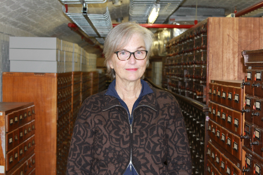Portrait of woman wearing glasses and brown shirt standing in a basement in front of wooden catalogue drawers