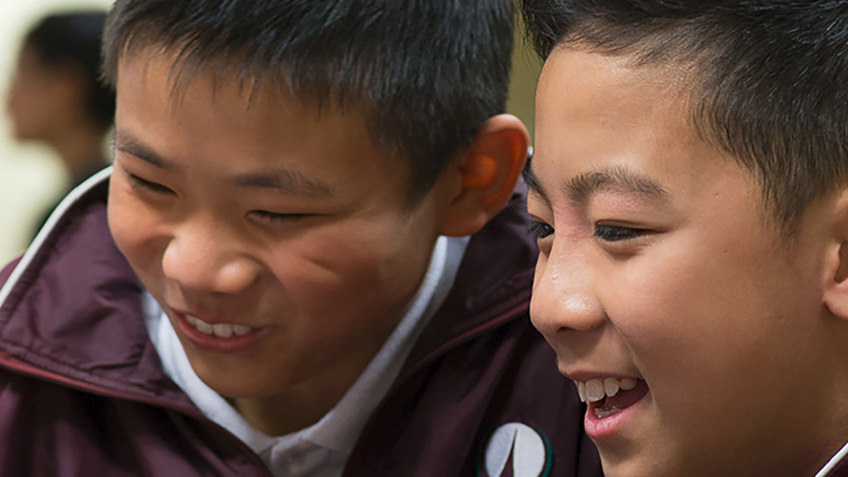 two Asian schoolboys laughing
