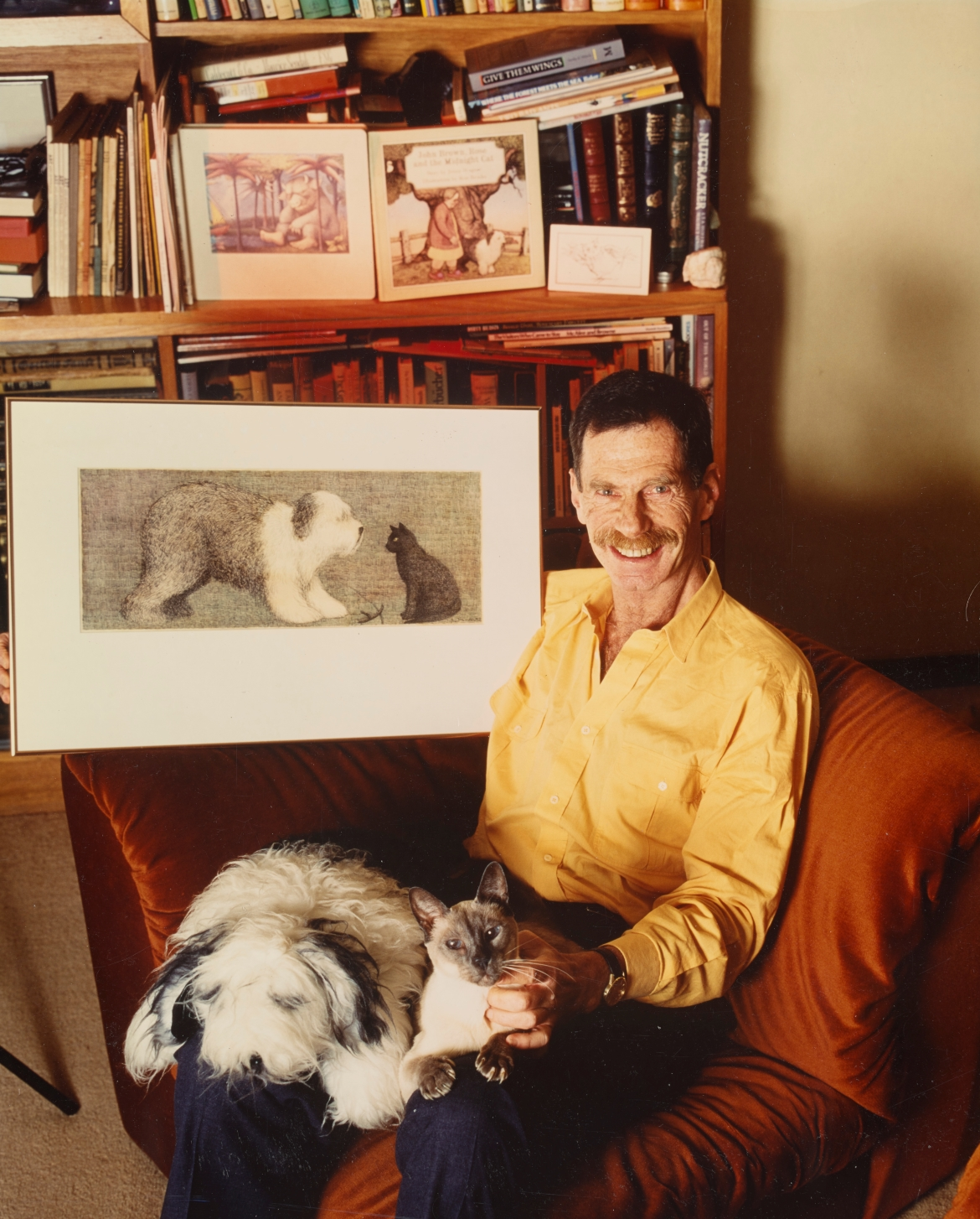 A smiling man sits with a fluffy dog on his lap