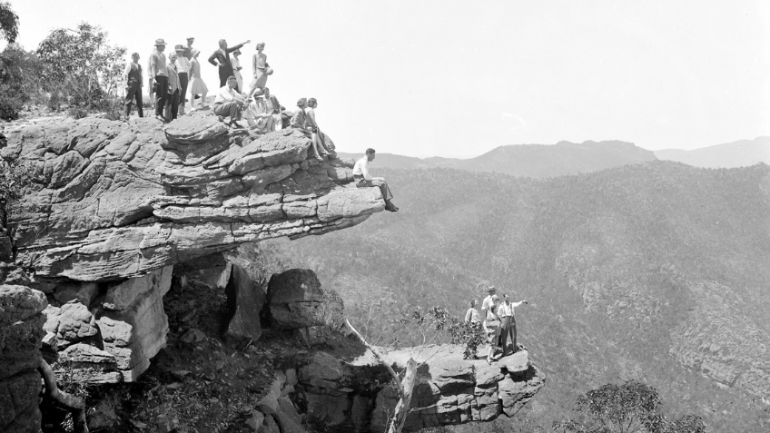 Black and white photo of people standing on a cliff face