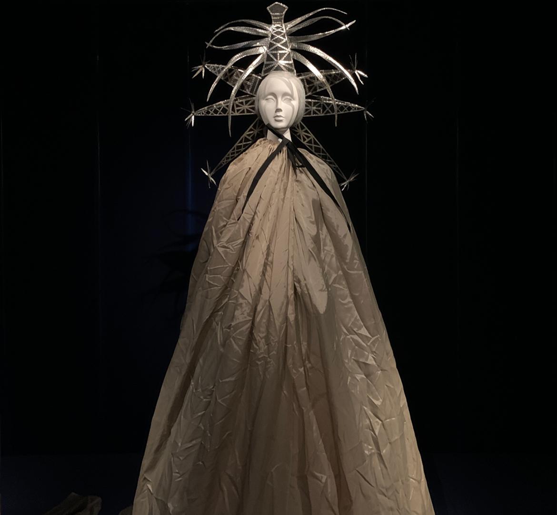 A mannequin wears a striking headress and a floor-length cloak