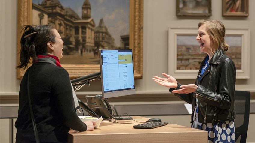 Two women laugh at a service desk in an art gallery