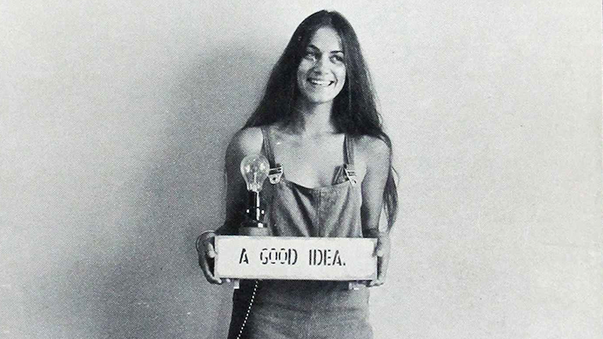 A long-haired, smiling woman in overalls holds up a sign saying 'A good idea'