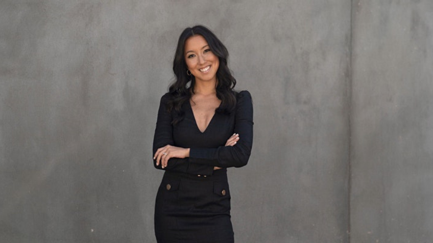 Woman smiling in black clothing in front of a grey wall