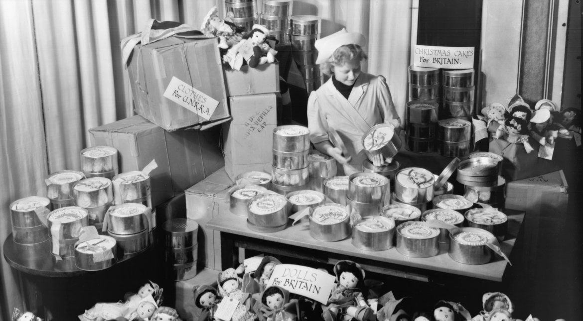 A woman in an apron and chef's hat stands behind a table piled with fresh cakes in baking tins