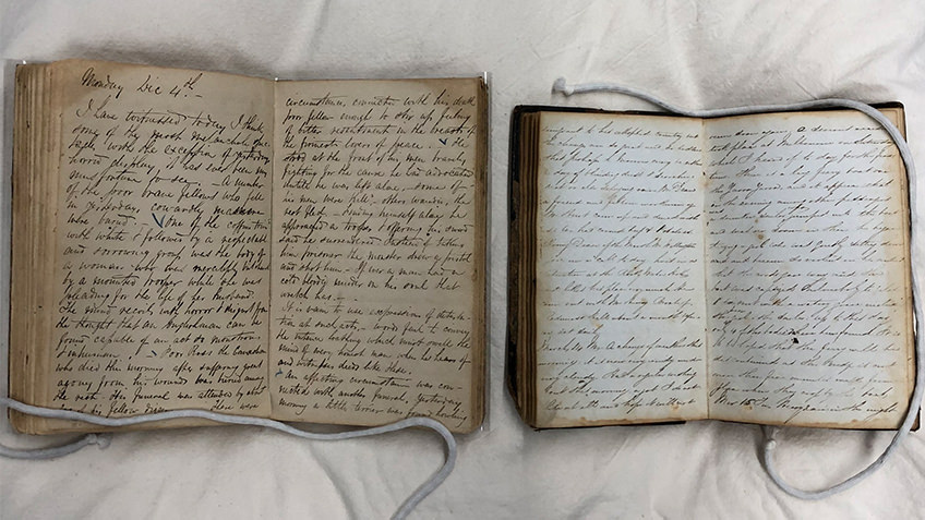 Two books lay open on a pillow, their pages filled with cursive handwriting