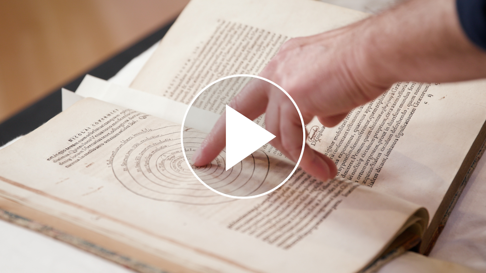 Open book with a hand tracing the words