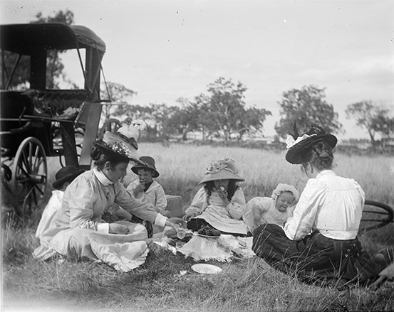 Two women in Edwardian clothes and two infants picnic on the grass beside a carriage