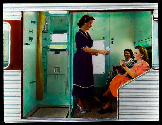 Two seated women and one standing have a drink within a small compartment beside a bathroom in a vehicle