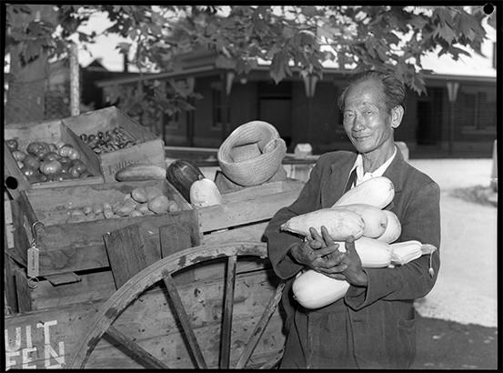 A Chinese man holding an armful of squash beside his wooden cart laden with vegetables