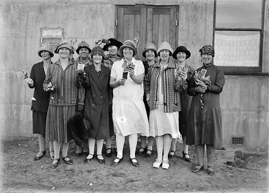 Nine women in 1920s-era clothes, hats and shoes smile and hold up paper money