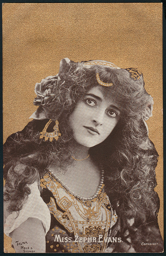 Face of a young woman with long, brown curly hair and large dark eyes