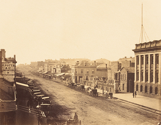 View of a wide, unpaved street with brick buildings, horses and carts on either side