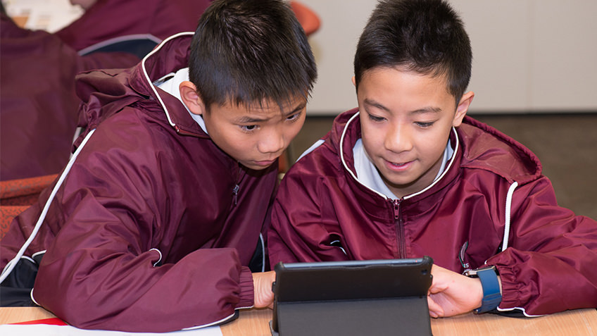 Two schoolboys in maroon jackets looking at a tablet