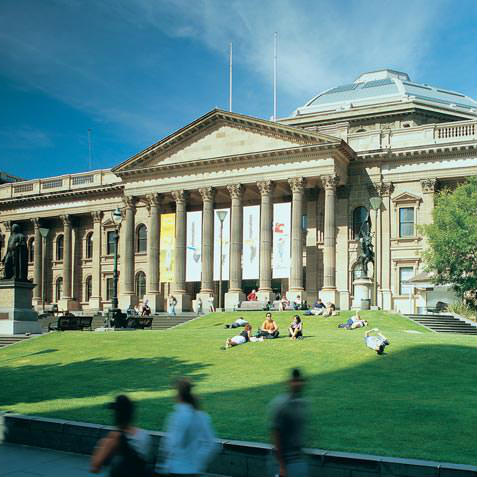 portico and facade of State Library Victoria with green grass and blue sky