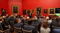 View from behind of people sitting in a red room filled with paintings