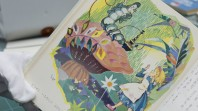 Open book with Japanese text and cartoon illustration of Alice in Wonderland with caterpillar