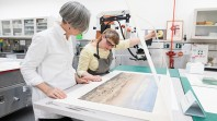 Colour photo of Liardet's watercolour being assessed by two staff in the State Library Conservation Lab
