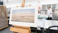 Colour photo showing Liardet's watercolour on an easel in the State Library's Conservation Lab awaiting assessment