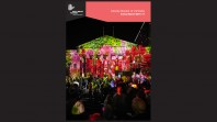 Colour cover of annual report showing front facade of Library with floral light projections on it and a crowd in the foreground