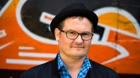 Bespectacled man wearing hat against swirling orange and black background