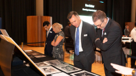 Four people in suits looking at old books