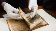 Hands flicking through an old book
