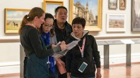 staff member helping visitors in artwork-lined Cowen Gallery