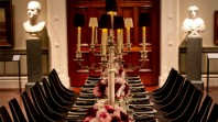 Colour photo of formal table setting with flowers, candelabra against backdrop of Cowen Gallery statues and doors