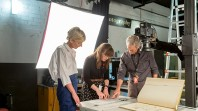 three people looking at a large book being photographed in a studio