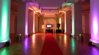 A gallery space with a red carpet, columns and multicoloured lights