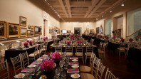 An art gallery is decorated with tables, chairs and flowers for an event