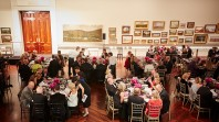 Waiters serve people in evening dress seated at tables in an art gallery