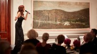 A red-haired female performer sings to an audience in an art gallery