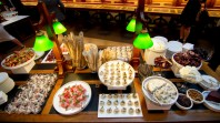 Colour photo of party food on plates in La Trobe Reading Room, displayed on a wooden desk under green table lamps