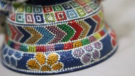 pot covered in brightly covered paint like beadwork with white accents