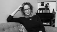 Black and white photo of woman with curly hair wearing glasses reclining on a sofa