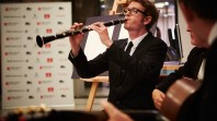 A man wearing glasses and a tuxedo plays clarinet to an audience