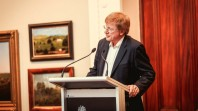 Colour photo of Kerry O'Brien speaking at ABA conference with Australian landscape paintings and red curtain