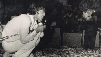 black and white 1960s photo of Mick Jagger crouching on the stage