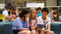 three children reading a book
