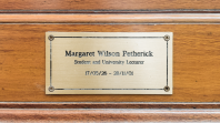 A bronze plaque inscribed to Margaret Petherick on a wooden background