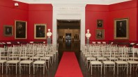 Colour photo of event seating against red carpet and walls of the portrait gallery, Red Rotunda