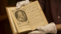 Colour photo of gloved hands holding a rare early edition of Jonathan Swift, Travels into several remote regions of the world…by Lemuel Gulliver, London, 1727