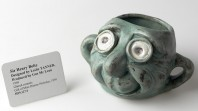 Ceramic mug in the shape of a man's face with a gallery catalogue card beside it