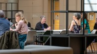 women at desks in public space